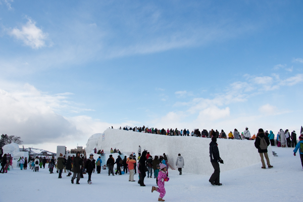 旭川冬まつりのロング滑り台の行列と脇の滑り台