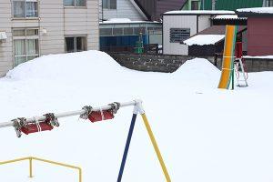 雪に備える公園のブランコと滑り台